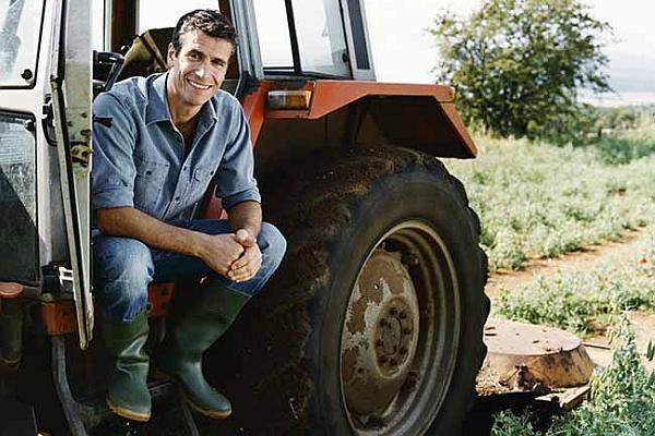 Farmer Sitting on a Tractor in a Field